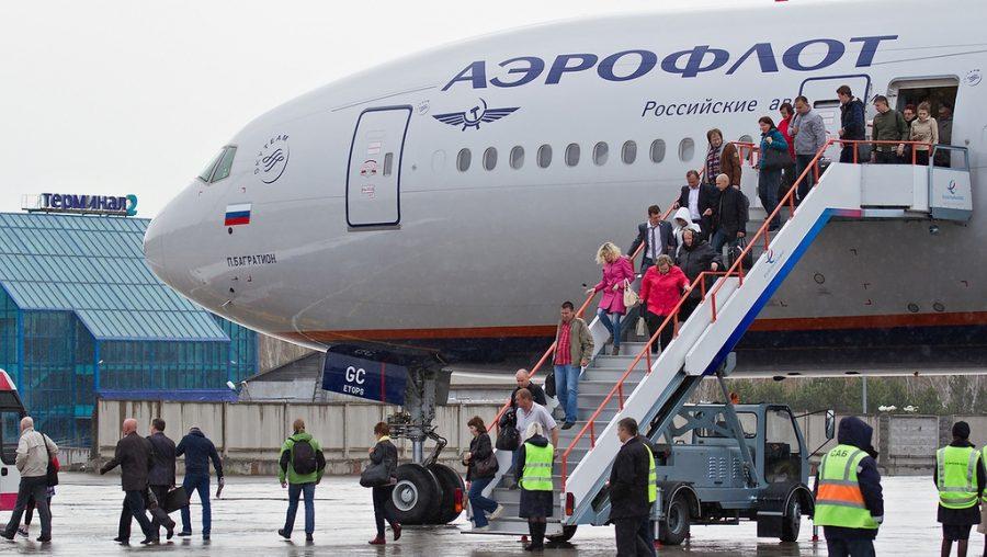 Пассажиры выходят из самолета
